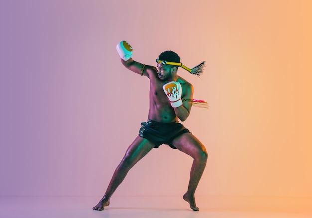 무에타이. 네온 불빛에 그라데이션 배경에 타이어 권투를 운동하는 젊은 남자.