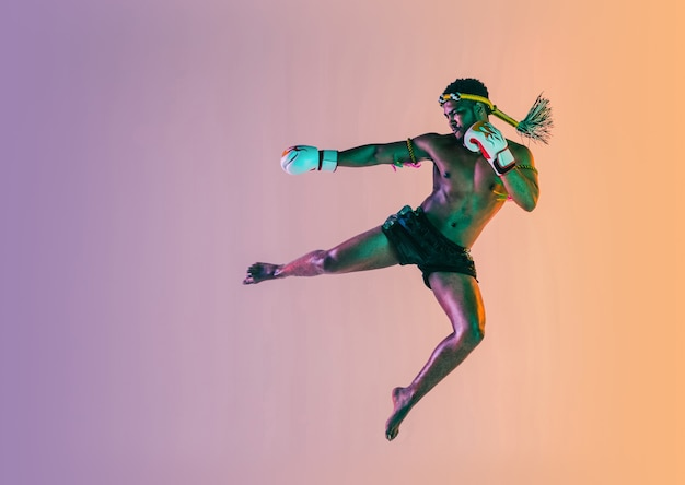 무에타이. 네온 불빛에 그라데이션 벽에 타이어 권투를 운동하는 젊은 남자. 전투기 연습, 무술 훈련, 동작. 건강한 라이프 스타일, 스포츠, 아시아 문화 개념.