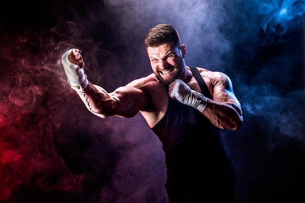 Боксер спортсмена muay тайский воюя на черной стене с дымом.