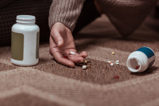 Much medicine. close up of woman lying on the floor committing suicide with taking meds