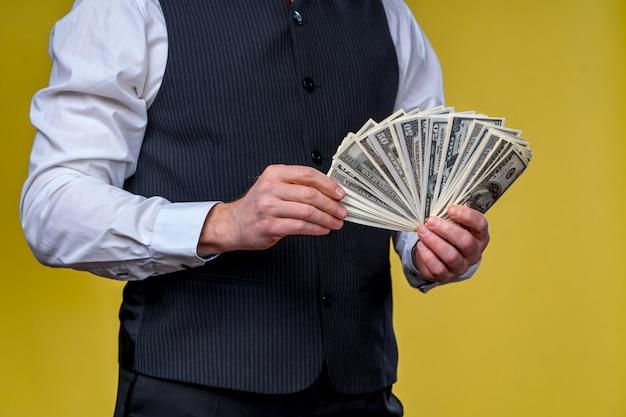 손에 많은 돈, 손에 달러. 남자는 달러를 보유하고 있습니다.
