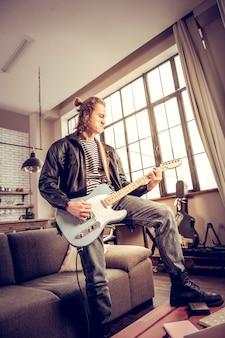 多くの満足。ロックミュージックを演奏することで多くの満足を得ている髪のお団子を持つ巻き毛の才能のあるミュージシャン