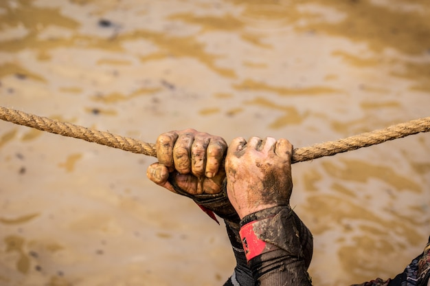 Mud race runners, defeating obstacles by using ropes. details of the hands.