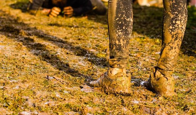 極端な障害物レース中に有刺鉄線障害物の下を通過する泥レースランナー