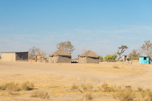 茂みに茅葺き屋根の泥わらと木造の小屋。ナミビア、アフリカ。