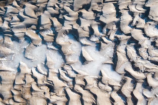 波と泥のテクスチャ。自然の中の泥を癒します。塩の背景。