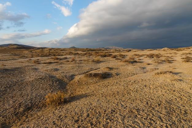 Mud volcanoes of gobustan near baku, azerbaijan. mud volcanic landscape against a stormy sky