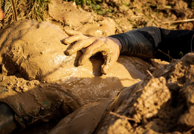 Muddy obstacle race runner in action. mud run. details of the hands.