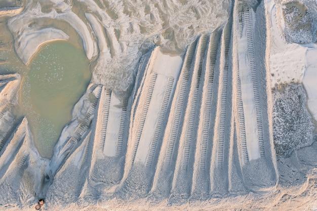 浚渫川の砂の採掘現場にある泥だらけの砂は、洗い流された川のサンにあるブルドーザーのトラックを水で濡らします...