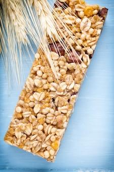 Батончики мюсли, зерновые батончики на деревянных фоне.