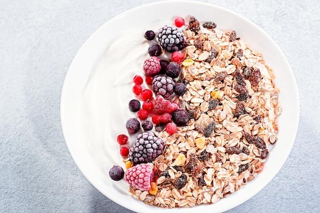 コンクリートのテーブルトップにヨーグルトとベリーを添えたミューズリーボウルまたはグラノーラボウル。健康的な朝食、上面図。ダイエットや健康的なライフスタイルに適した料理