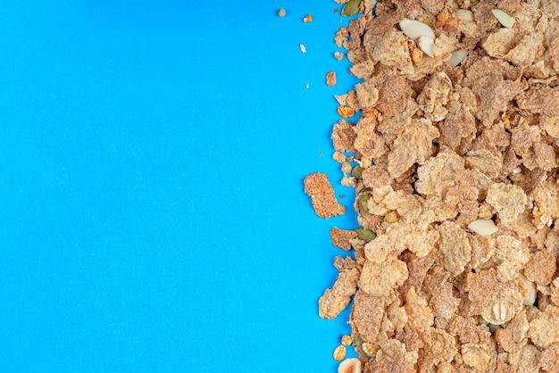 ミューズリーのクローズアップがテーブルに散らばっている青い背景の朝食用シリアル健康食品ba ...