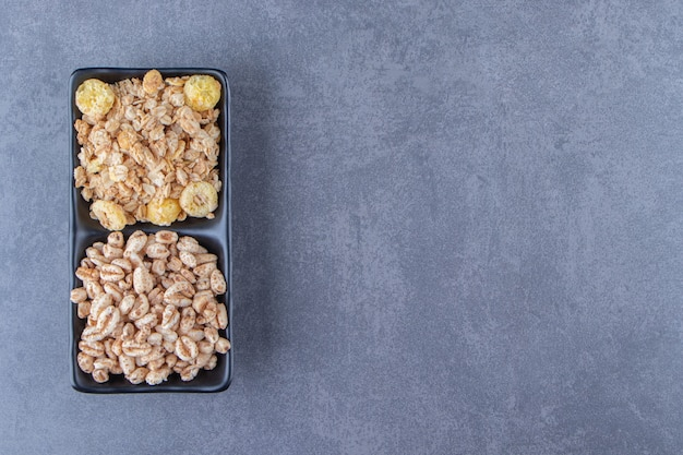 Muesli and cornflakes in bowls, on the marble background. high quality photo