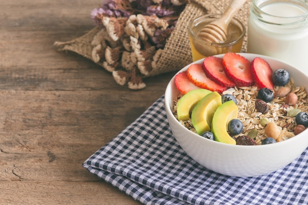 Muesli or granola on with fresh fruits nuts and cereal served with milk and honey