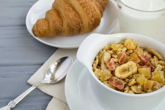 Muesli, milk and croissant on the grey  wooden background