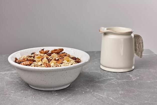石のテーブルの上の白いボウルにドライフルーツとピーカンナッツのミューズリーまたはグラノーラ。