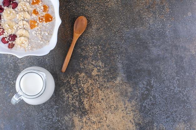 Porridge di muesli con frutti di bosco e un vasetto di latte