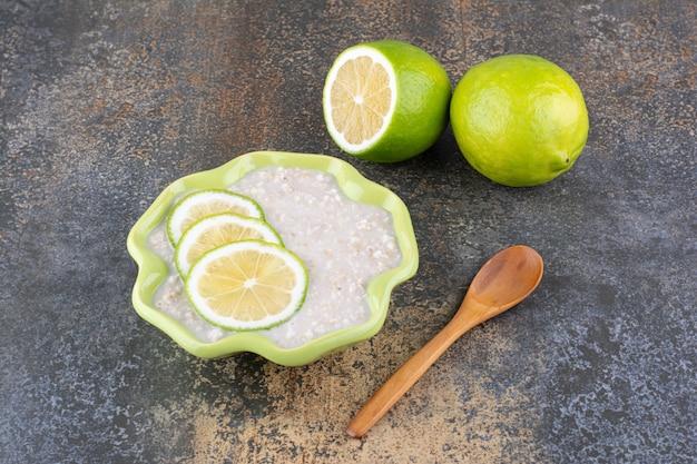 Каша мюсли с дольками лимона в зеленой тарелке
