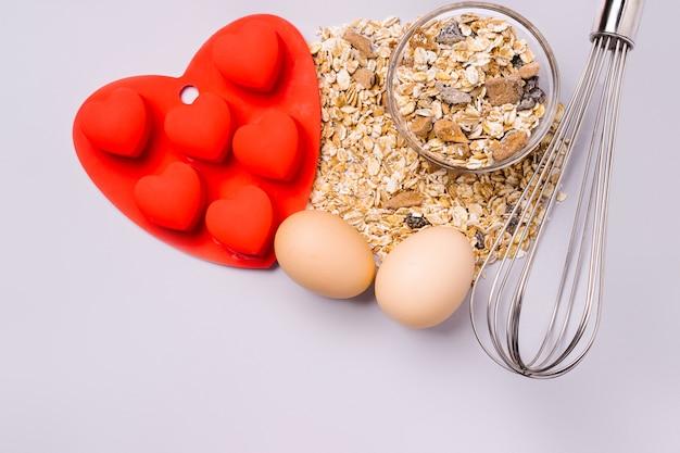 ミューズリー、泡立て器、ベーキング皿、究極の灰色の背景においしいバレンタインデーのサプライズを作ります。