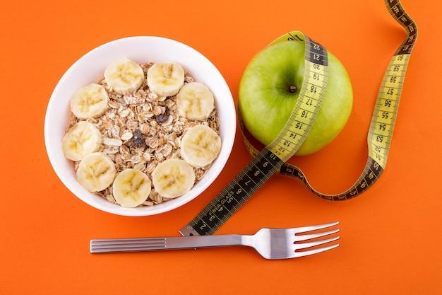 오렌지 표면에 있는 흰색 접시에 바나나를 넣은 뮤즐리 포크와 녹색 사과