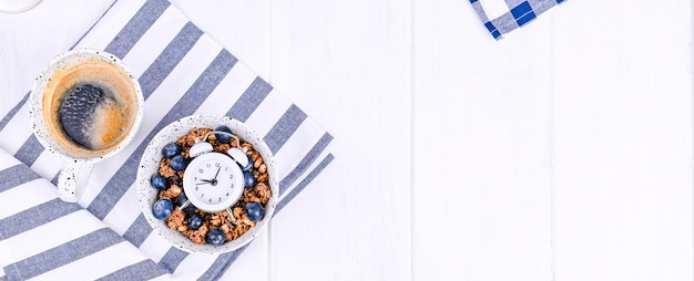 Muesli with blueberries in a cup and aromatic morning coffee. breakfast on a white wooden background and an alarm clock. flat lay. banner