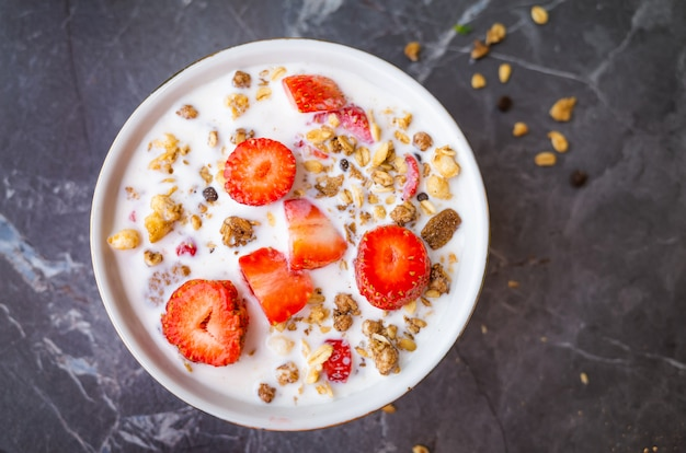 Muesli with chocolate and fresh strawberries with milk in a plate on a dark gray background.