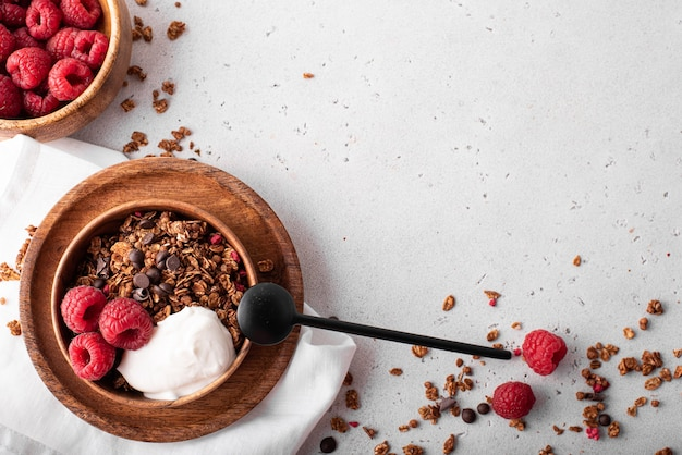 Muesli with chocolate, nuts and fresh raspberries in wooden bowls, top view