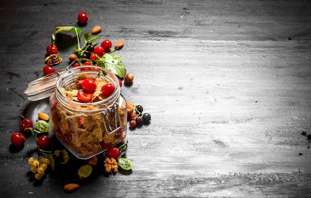 Мюсли с лесными ягодами на черном деревянном фоне