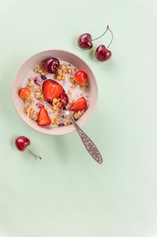Мюсли со свежими фруктами и йогуртом. каша со свежей клубникой и вишней