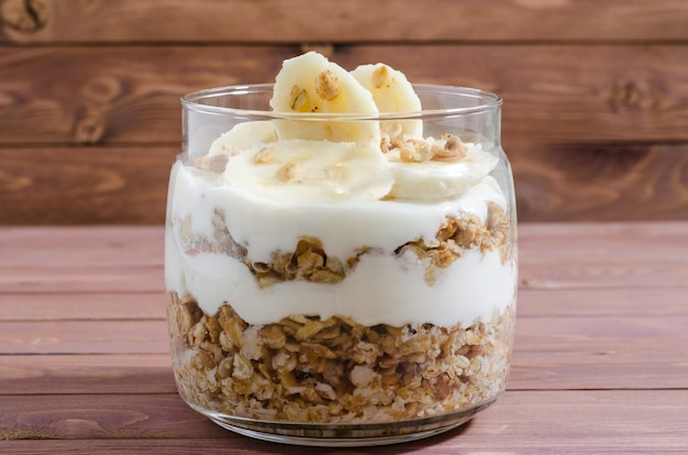 Muesli with natural yoghurt, banana, nuts and dried fruits in a glass jar