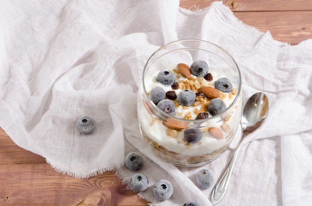 Muesli with natural yoghurt, blueberry, nuts and dried fruits in a glass jar