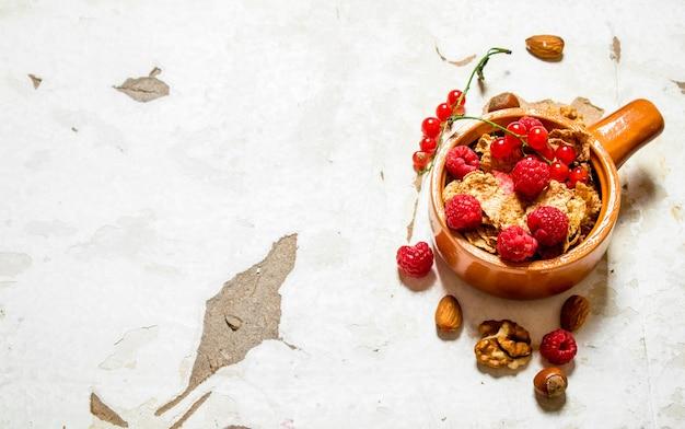 Мюсли со спелой малиной и орехами на деревенском фоне