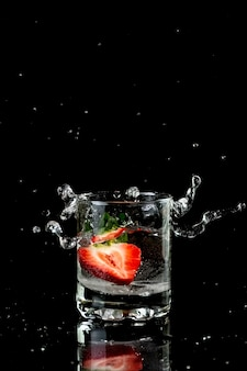 Muesli with yogurt and berries in a glass on a white background