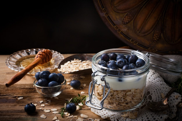 Muesli with yogurt and blue berries in glass jar.
