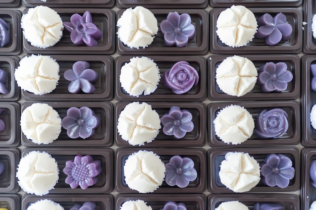 マフィンカップケーキまたはコットンウールケーキパープルペーストと甘いデザートバナナをトレイにダークブラウンで置きます。
