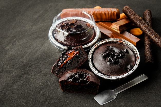 Muffin dark chocolate lava with chocolate chip in foil tray bread with plastic spoon