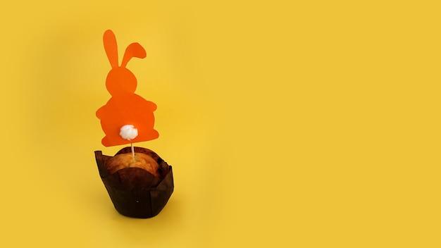 つまようじに紙うさぎで飾られたマフィン。カップケーキのイースターの装飾。お祝いのお菓子やペストリー。黄色の背景