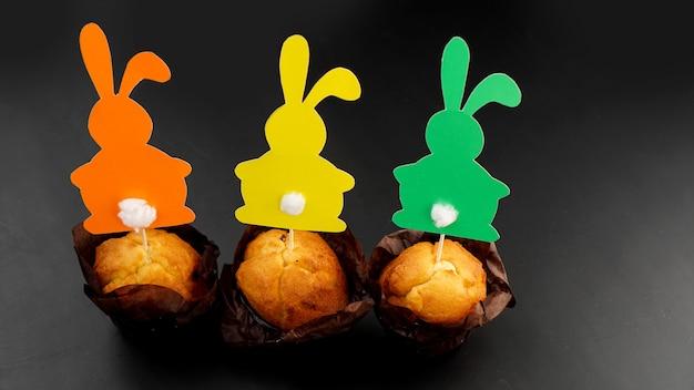 つまようじに紙うさぎで飾られたマフィン。カップケーキのイースターの装飾。お祝いのお菓子やペストリー。