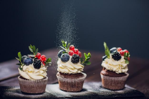 Muffin decoration .no powdered sugar. woman confectioner throws powder