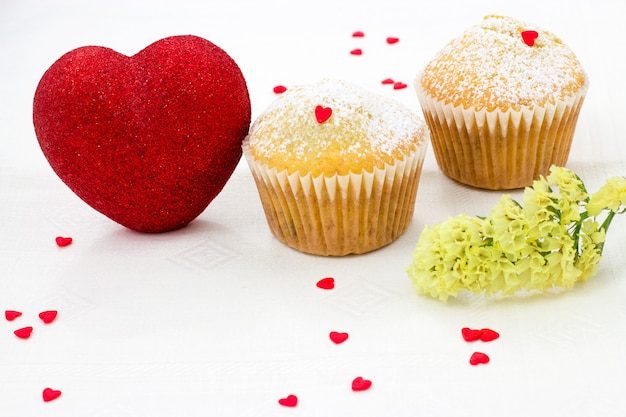 Muffin tins in paper, sprinkled with with icing sugar, red shiny heart and lot small sugar hearts on a white