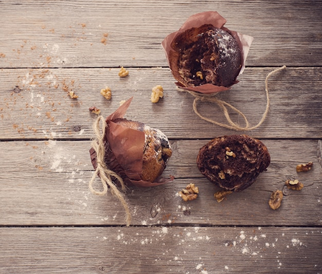 Muffin with chocolate on wooden background