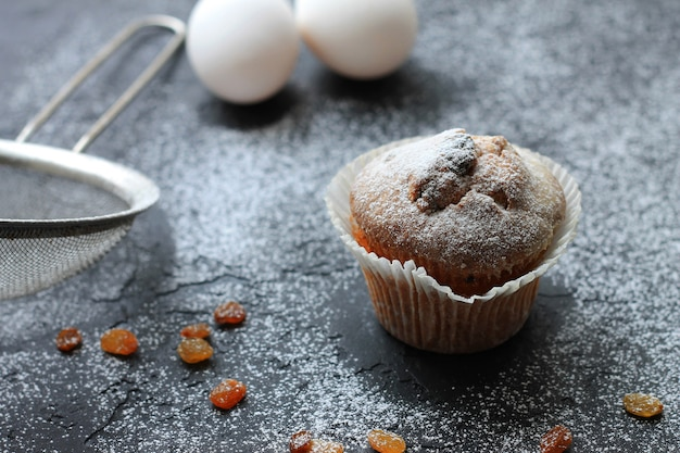 Muffin with raisins sprinkled with powdered sugar on a wooden background and are ingridient on the a blurry background