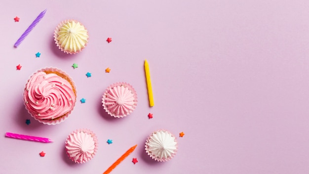 Кексы; свечи; aalaw и брызгает на розовом фоне