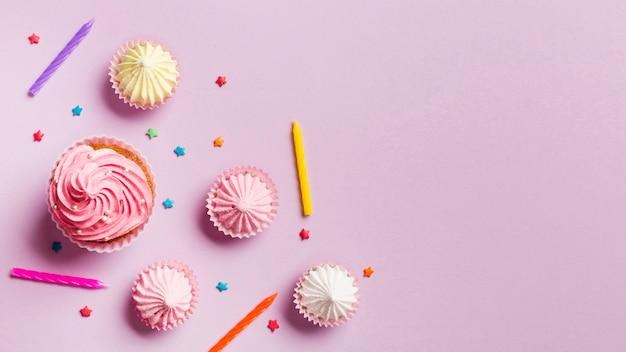 Muffin; candele; aalaw e spruzza su sfondo rosa