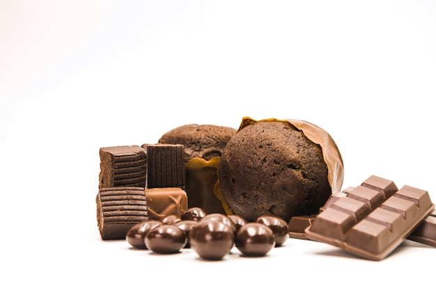 Muffins; chocolate bar and balls on white background