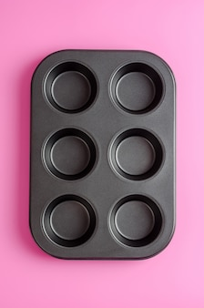 Muffins and cupcakes baking tin on a pink background.