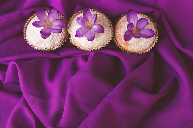 紫色の背景にクロッカスの花で飾られたマフィン。春。上面図。コピースペース。