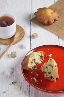 赤いプレートのマフィン、白い木製のテーブルの上のお茶と角砂糖のカップ