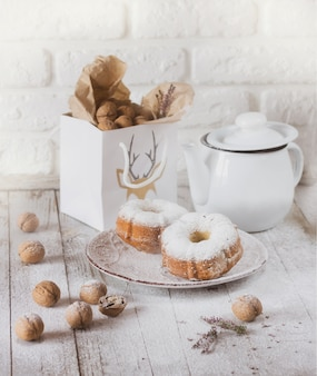 Muffins, nuts and teapot on white table