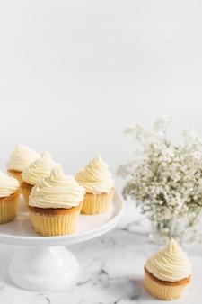 白い背景のケーキスタンドのマフィン